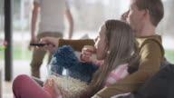 istock Family eating popcorn and watching TV 660729242
