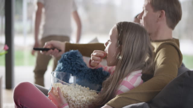 Family eating popcorn and watching TV Medium handheld shot of a boy bringing popcorn in a bowl to family members sitting on the sofa and he sits and watches TV with them. Shot in Slovenia. family watching tv stock videos & royalty-free footage