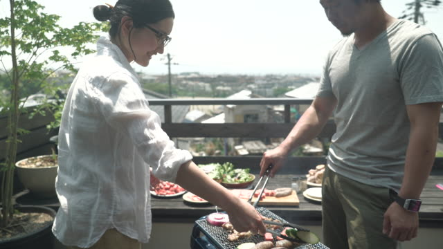 Family enjoying a barbecue on the terrace Family enjoy a barbecue on holiday. barbecue meal stock videos & royalty-free footage