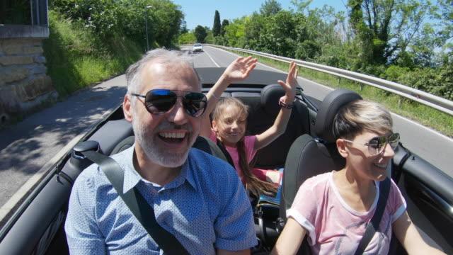 vídeos de stock, filmes e b-roll de família que aprecia uma viagem por estrada com um carro convertível - veículo terrestre