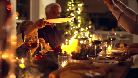 Family enjoying Christmas dinner together Christmas eve dinner, family sitting at dining table enjoying dinner together. Family celebrating christmas together at home. christmas stock videos & royalty-free footage