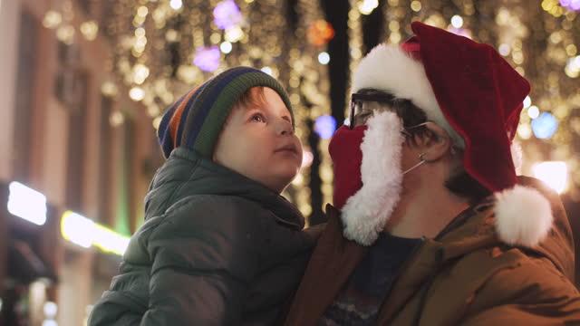 covid-19 전염병 동안 도시 거리에서 크리스마스 조명을 즐기는 가족 - christmas decorations 스톡 비디오 및 b-롤 화면
