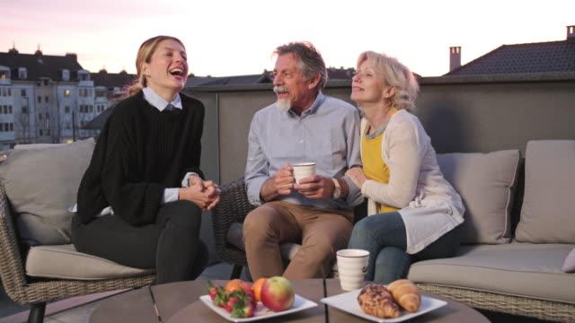 family enjoying coffee and snacks on a terrace - terrazza video stock e b–roll