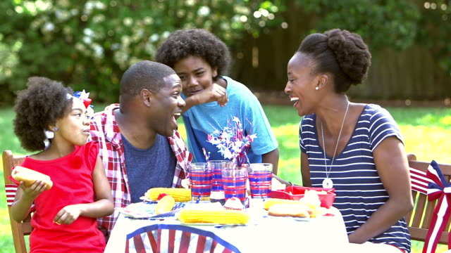 Family enjoying Memorial Day or 4th of July picnic An family with two children having a cookout in their back yard on the fourth of july or memorial day.  They are sitting at a table decorated in red, white and blue patriotic colors. They are eating, talking and laughing together. family 4th of july stock videos & royalty-free footage