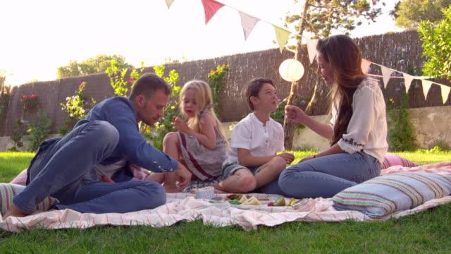 家族の庭で毛布の上でピクニックを楽しんで ビデオ