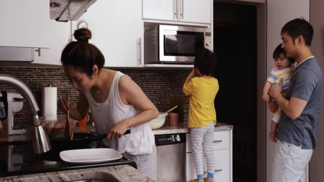rodzina ciesząc się czasem relaksu razem w domu - piec przygotowywać jedzenie filmów i materiałów b-roll