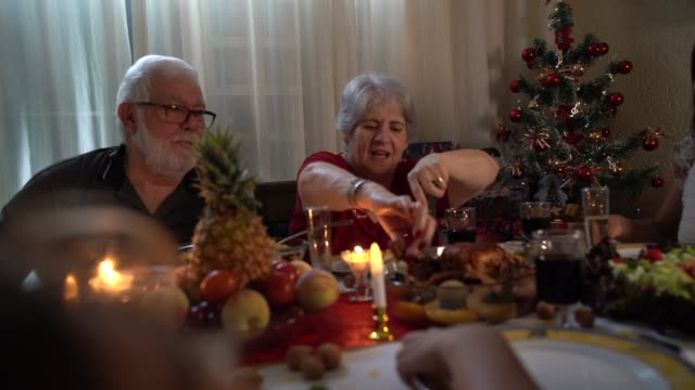 la famiglia gode della cena di natale a casa - pranzo di natale video stock e b–roll