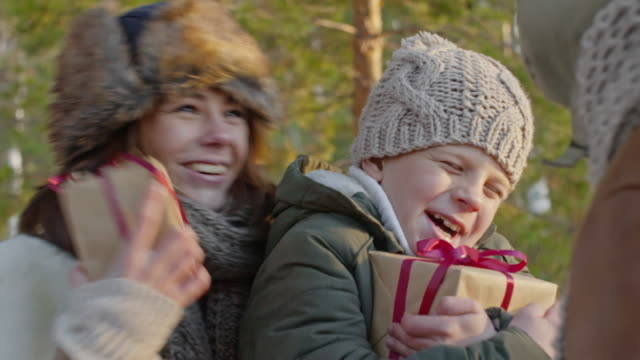 Family Exchanging Gifts Outside Happy young woman and little boy holding presents and hugging and kissing man in winter forest gratitude stock videos & royalty-free footage