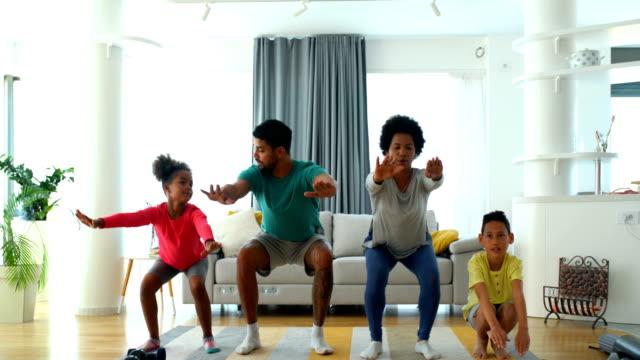 vídeos de stock e filmes b-roll de family exercising at home - agachar se