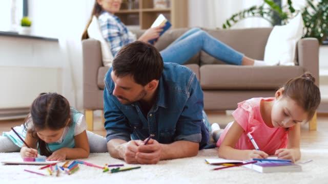 vídeos de stock, filmes e b-roll de família, paternidade e conceito do lazer-pai que gasta o tempo com suas filhas pequenas que desenham nos sketchbooks por pastéis e que encontram-se no assoalho em casa - fathers day