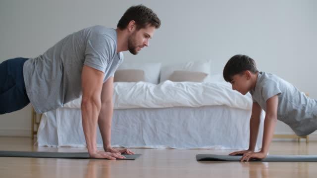 vídeos de stock e filmes b-roll de family fitness at home, father coach, sports kid, fun gymnastics - treino em casa