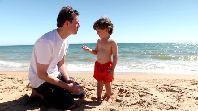 family fun applying sun cream – father and son - sun cream stock videos & royalty-free footage