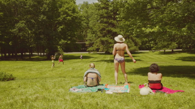 Family fun at the summer's picnic: teenager girls and young man playing with water Family fun at the summer's picnic: teenager girls and the young man playing with water and three adult women watching them. 4K UHD video footage. Poconos, Pennsylvania, USA sunbathing stock videos & royalty-free footage