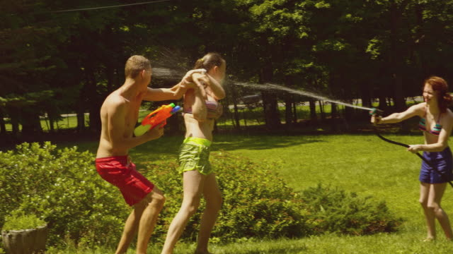 Family fun at the summer's picnic: teenager girls and young man playing with water video