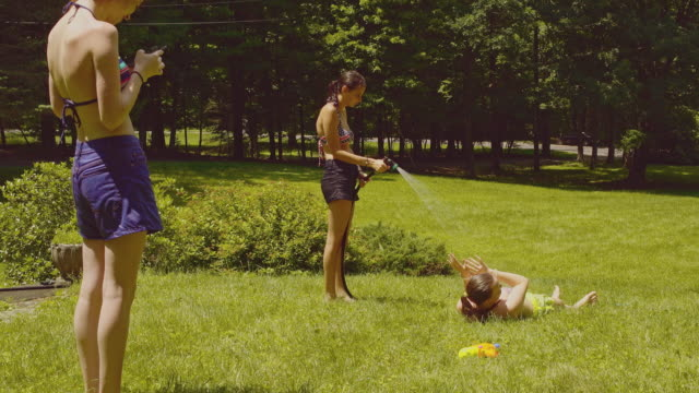 Family fun at the summer's picnic: teenager girls One girl watering the other, and third filming it with the smartphone. video