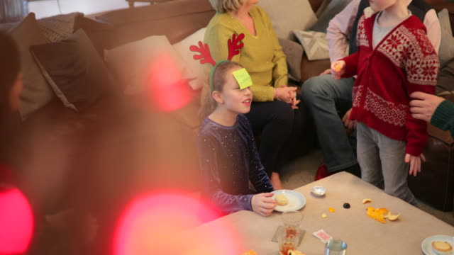 Family Fun Night Family with sticky notes stuck on their heads playing a party game at Christmas. They are all laughing and having fun. They are also eating mince pies and tangerines. christmas fun stock videos & royalty-free footage