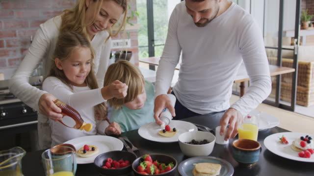 快適な家4kのダイニングテーブルで食べ物を飾る家族 - 食事する点の映像素材/bロール