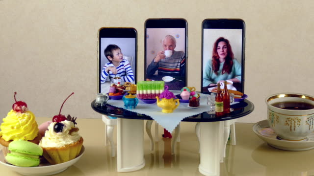 Bидео family gathered for tea at a toy table using video connection