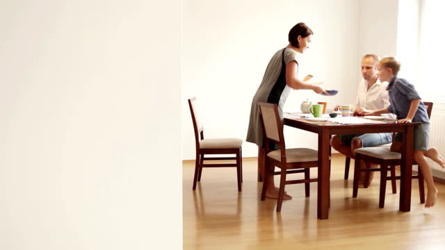 Family gathers at the table for breakfast: mother is serving food Family gathers at the table for breakfast: mother is serving food brightly lit stock videos & royalty-free footage