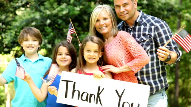 Family gathers to celebrate patriotic holiday Family of Five gathers to celebrate a patriotic holiday with flags and a large THANK YOU sign for veterans and the military. family 4th of july stock videos & royalty-free footage