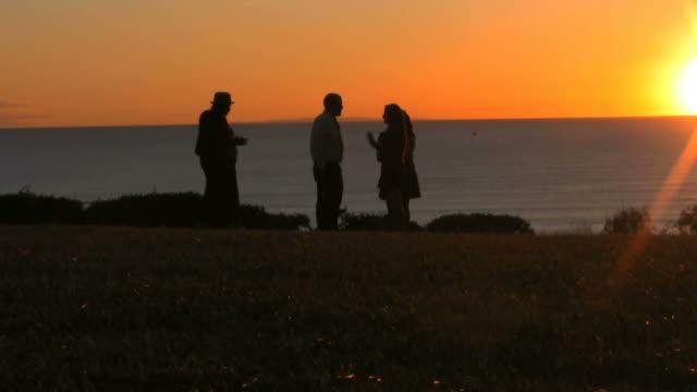 Familia recopila para disfrutar de la puesta del sol con vista al mar - vídeo