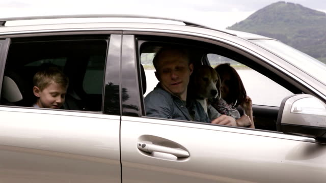 Family gets in a car with their dog and continue to ride video