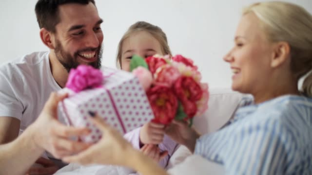 family giving flowers and gift to mother in bed - mothers day stock videos & royalty-free footage