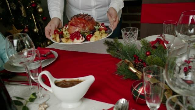 vídeos y material grabado en eventos de stock de familia con cena de navidad con jamón esmaltado vacaciones con clavos, verduras picada empanadas y ponche de huevo naranja bagatela - ornamentado