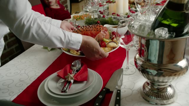 vídeos de stock e filmes b-roll de family having christmas dinner with glazed holiday ham with cloves, vegetables, minced pies and eggnog orange trifle - presunto