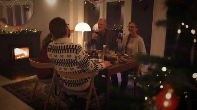 Family having Christmas eve dinner European family sitting at dinner table having a Christmas eve dinner together. Interior shot of warm cozy Christmas decorated family home. christmas decoration stock videos & royalty-free footage