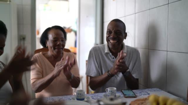 stockvideo's en b-roll-footage met familie die koffie samen heeft en bij keuken applaudisseert - breakfast table