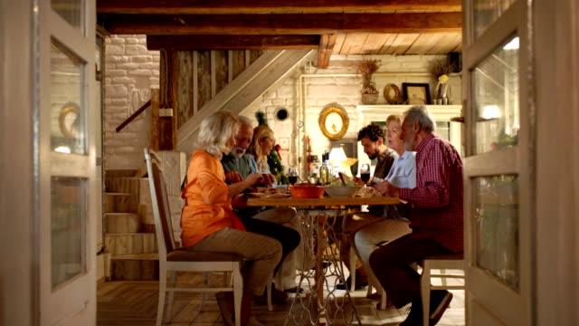 family having dinner on christmas eve. - pranzo di natale video stock e b–roll