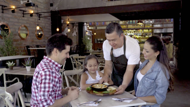 Family having fun at a restaurant while happy waiter serves an appetiser video