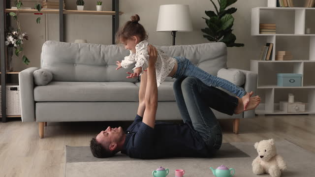 Family having fun at home father plays with little daughter