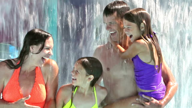 Family having fun at water park under waterfall video