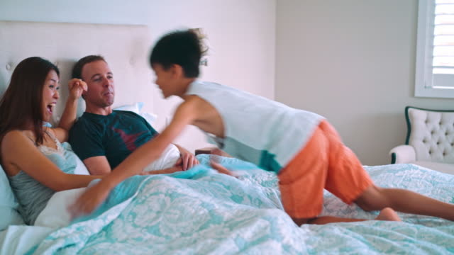 Family having fun in the bed video