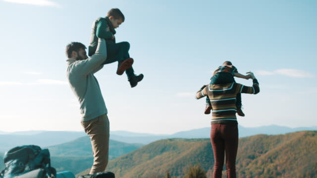 Family having fun on field on top of the mountain video