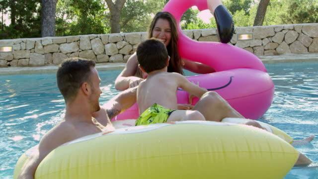 屋外スイミング プールに空気で膨らます上で楽しんで家族 - ヴィラ点の映像素材/bロール