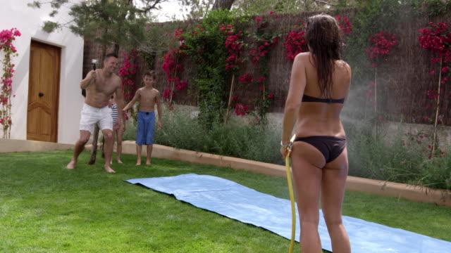 Family Having Fun On Water Slide In Garden Shot On R3D video