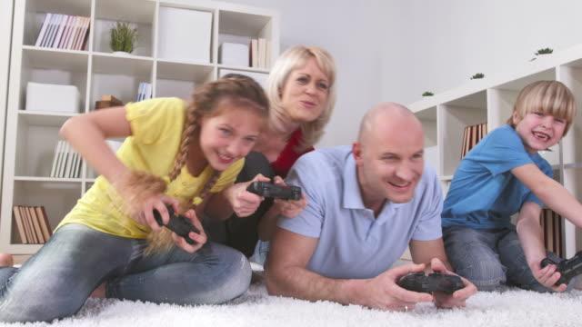 hd dolly: семья весело играя в видео игры - развлекательные игры стоковые видео и кадры b-roll