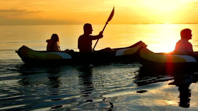 TS familia divirtiéndose kayak de mar en la puesta de sol - vídeo