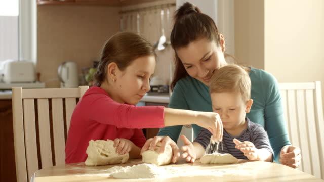 Familie Spaß Zeit kochen zusammen kneten Teig am Küchentisch und seine Mutter unterrichten von Kindern – Video
