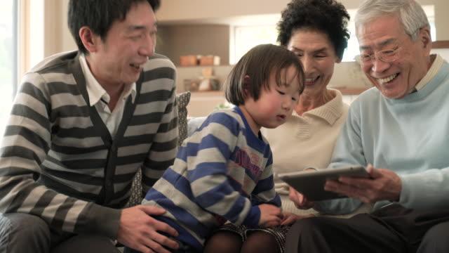 stockvideo's en b-roll-footage met familie plezier met behulp van een digitaal tablet samen thuis - oost azië