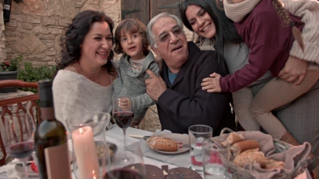 семья весело провести время с бабушкой и дедушкой на семейной трапезе - средиземноморская культура стоковые видео и кадры b-roll