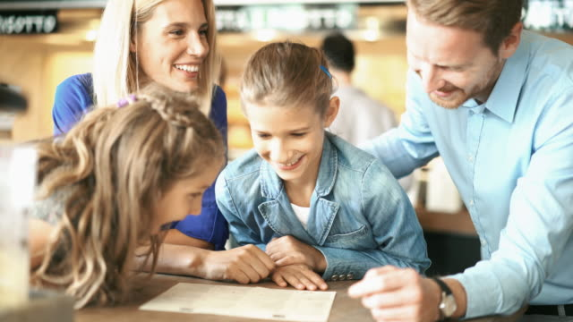 Family having lunch at a restaurant. Closeup of a young family with two daughters having lunch at a restaurant. They are reading the menu and deciding what they should order. fork stock videos & royalty-free footage