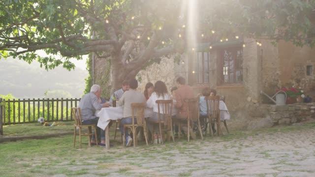 familie zu mittag am esstisch im garten - gartenparty stock-videos und b-roll-filmmaterial