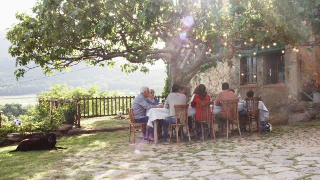 familjen ha lunch av träd utanför huset på gården - spain solar bildbanksvideor och videomaterial från bakom kulisserna