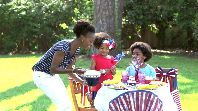 Family having Memorial Day or 4th of July picnic An African-American woman and her two children having a cookout in their back yard on the fourth of july or memorial day.  The little girl, 7 years old, has a patriotic bow in her hair. Mom walks up and with a bowl of fruit salad. family 4th of july stock videos & royalty-free footage