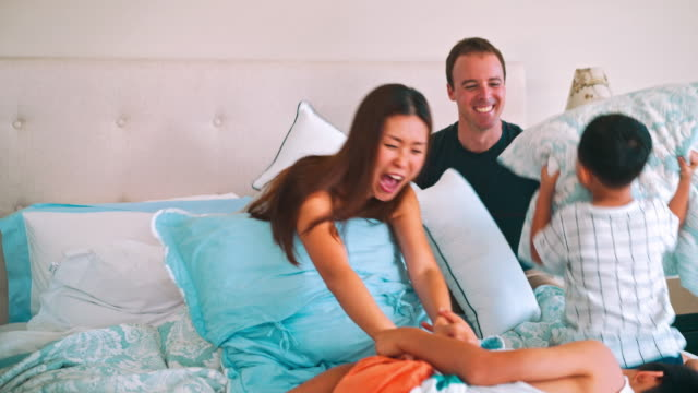 Family having pillow fight in the bed video