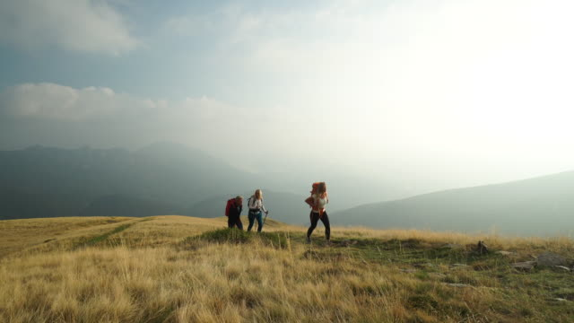 family hike along mountain top with backpacks - trekking video stock e b–roll